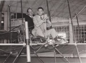 CAB chairman Alan Boyd, rear, and FAA Administrator Najeeb Halaby, front, in what appears to be a Wright Brothers flyer replica.